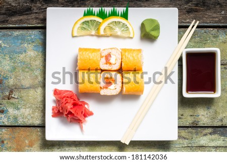 Seafood Sushi rolls in White Long Dish with soy sauce on old wooden table - stock photo