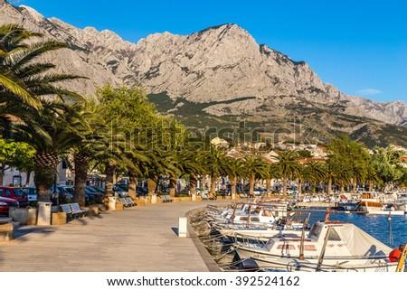 Seafront Promenade With Yachts And Palms And Biokovo Mountain In The Background  - Baska Voda, Makarska, Dalmatia, Croatia - stock photo