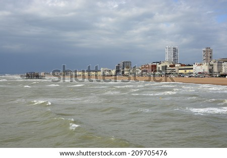 Seafront with ruined West Pier at Brighton. East Sussex. England. Stormy sky and rough sea. - stock photo