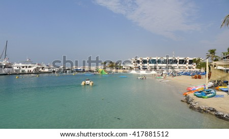 seafront with the pure white sand beach and crystal clear water surrounded by green palm trees in middle east - stock photo