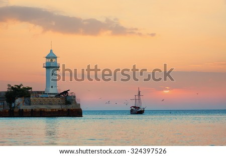 Seagulls fly round masts of the sailing ship coming into a bay on a sunset