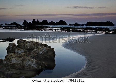 Seal Beach sea stacks along the Oregon coast beyond the beach at sunrise - stock photo