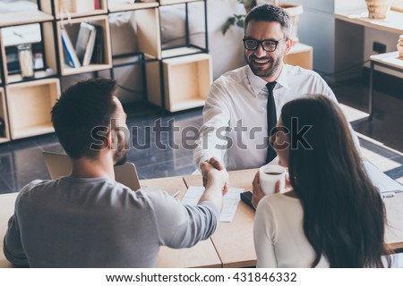 Sealing a deal. Top view of two men sitting at the desk and shaking hands while young woman looking at them and smiling  - stock photo