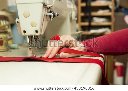 Seamstress hand supporting a piece of red cloth being fastened to satin ribbon by a sewing machine - stock photo