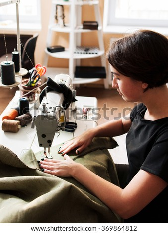 seamstress making clothes. Workplace tailor - sewing machine, rolls of  thread, fabric, scissors. - stock photo