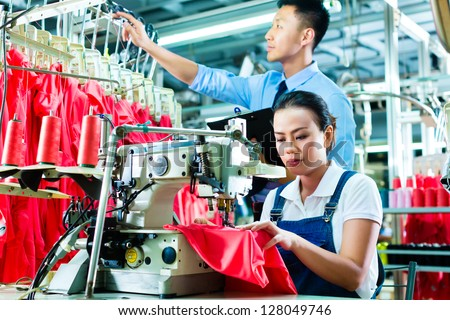 Seamstress or worker in a factory sewing with a sewing machine, a foreman checks the yarn - stock photo