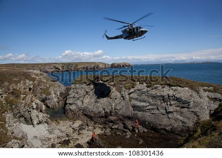 Search and Rescue Training  with a winchman hanging on the end of a wire RAF Valley Anglesey UK