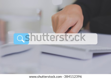 search bar on a virtual screen with his finger activating a global online computer search for a website - stock photo