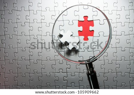 Search for missing puzzle pieces with a magnifying glass. Concept image of detecting a defect. - stock photo