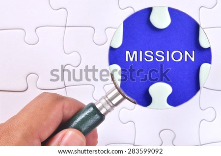 "Searching for missing ""Mission"" word puzzle using the magnifying glass  - stock photo"