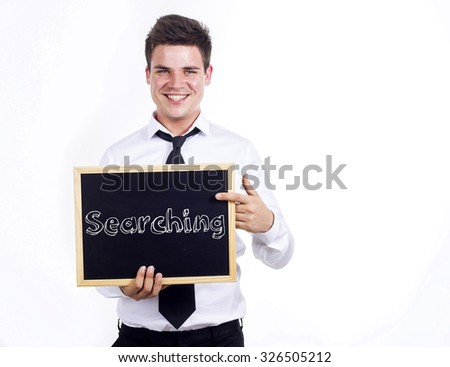 Searching - Young smiling businessman holding chalkboard with text - stock photo