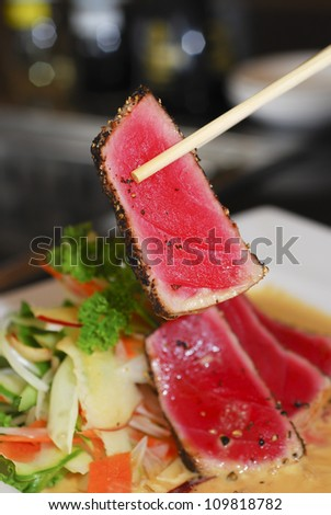 Seared Tuna holding with chopsticks - stock photo