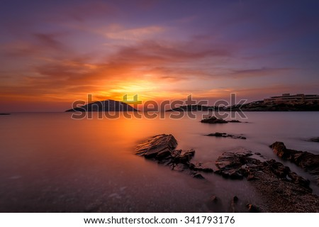 Seascape against a spectacular and colorful sunset with dreamy clouds passing over the bay mirroring on the rocks, long exposure shot - stock photo
