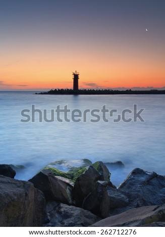 Seascape at sunset - lighthouse on the coast. - stock photo