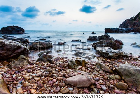 Seascape coast of evening wave with rock and cloud on blue sky - stock photo