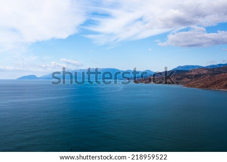 seascape from the top on a cloudy day with mountains on the horizon - stock photo