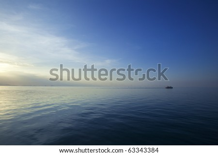 Seascape in the middle of the Ocean with Sun setting on one side and a boat moving away from it! Beautiful color contrast in the Golf of Thailand! - stock photo