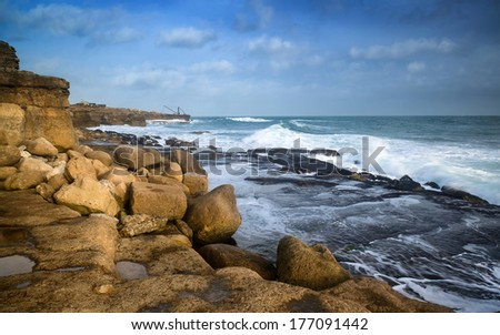 Seascape landscape of waves crashing onto rocks during beautiful Winter's day - stock photo