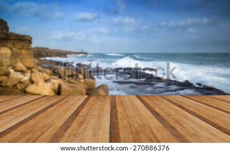 Seascape landscape of waves crashing onto rocks during beautiful Winter's day with wooden planks floor - stock photo