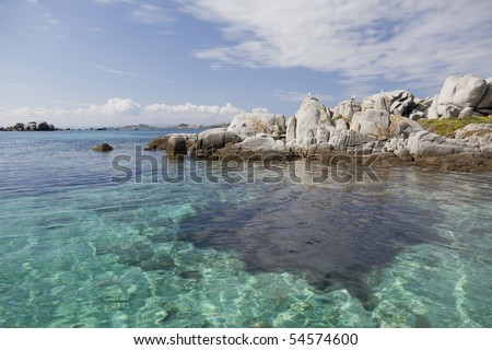 Seascape of shallow water and dramatic rocks.
