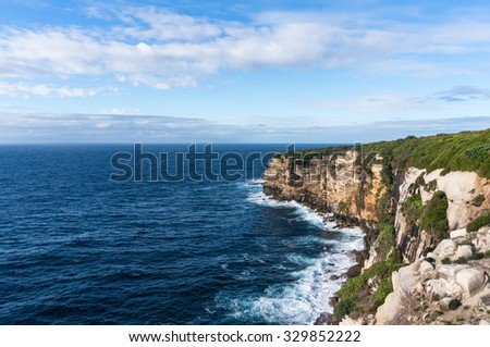 Seascape of steep and rugged cliff with bush and trees and Pacific Ocean. Royal National Park, NSW, Australia.  - stock photo