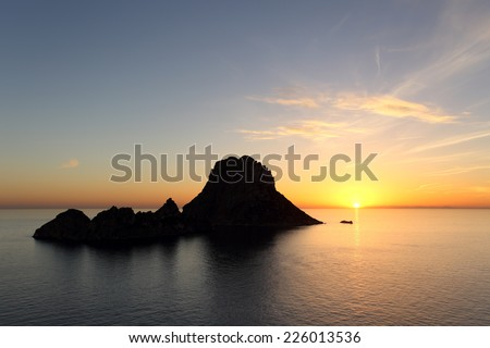 Seascape of sunset on Es Vedra in Ibiza island Baleares Spain - stock photo
