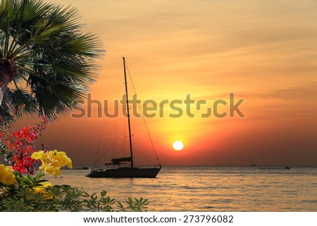 seascape scenic sunset and anchored boat with deflated sails off the coast of Thailand - stock photo
