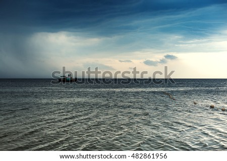 Seascape. Sea boat on the background of a cloudy sky before the storm