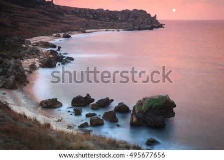 Seascape. Seashore with misty water at sunset