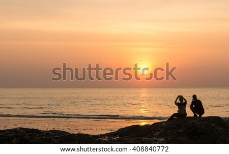 Seascape, silhouette couples sitting on rock captured their memory at sunset. - stock photo
