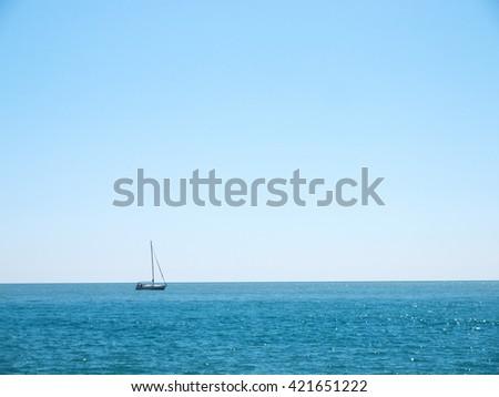 Seascape sunny day with yacht on horizon - stock photo