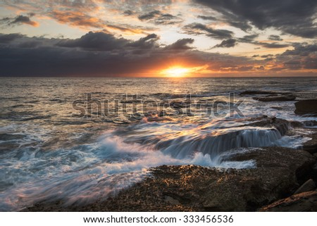 Seascape sunrise long exposure with waterfall over rock water and bright sky with sun