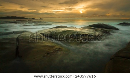 Seascape sunset with long exposure on the rocks. - stock photo