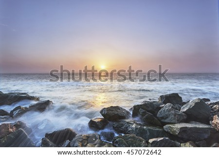 seascape sunset with rocks and little lighthouse. Long exposure