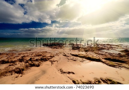 Seascape with dark sky and sand and horizon