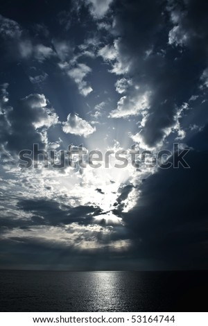 Seascape with dramatic sky and  sun-rays get through the clouds - stock photo