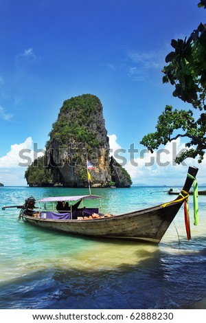 Seascape with exotic island and long tail boat in Thailand - stock photo
