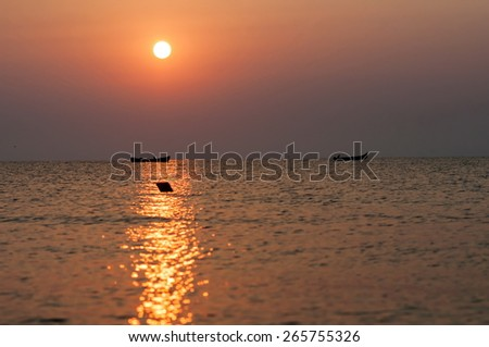 Seascape with fishing boat at sunset - stock photo