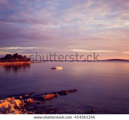 Seascape with Lonely Boat in Sea at Sunset - stock photo