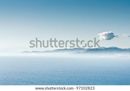Seascape with mountains in the background and sky blue