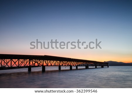 Seascape with old steel bridge in twilight time