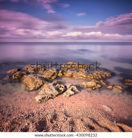 Seascape with rocks and sand in the foreground with two ships on the horizon. Long exposure - stock photo