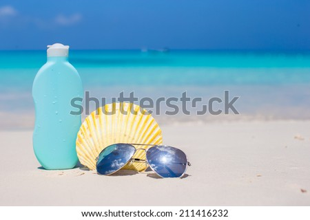 Seashell, sunglasses and suncream on white sand - stock photo