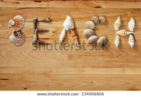 Seashells arranged to spell the word 'BEACH' on wood background with copy space. - stock photo