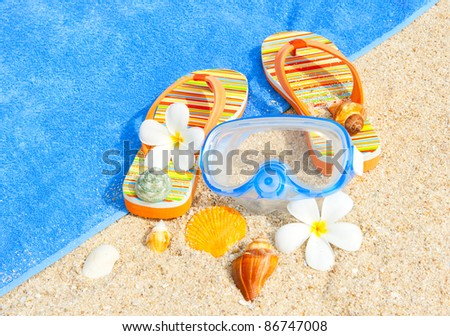 Seashells, diving mask and sandalls on the beach - stock photo