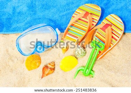 Seashells, diving mask and sandals on the beach - stock photo