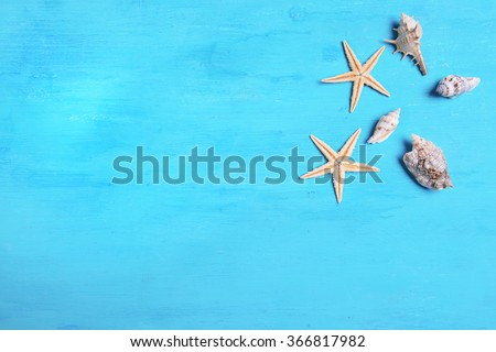 Seashells on blue wooden background - stock photo