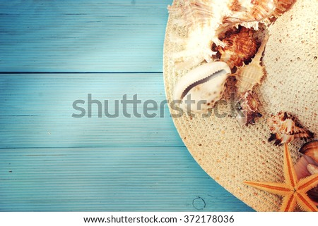 Seashells on blue wooden plank with straw hat and flip-flop  - stock photo
