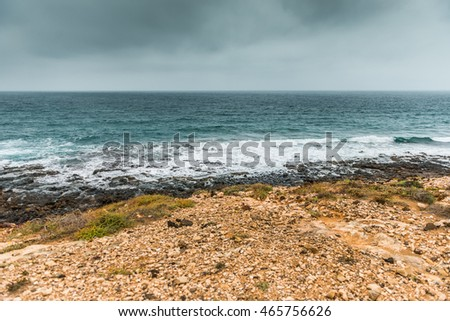 seashore in Lanzarote in gloomy weather with horizon on the background, Spain
