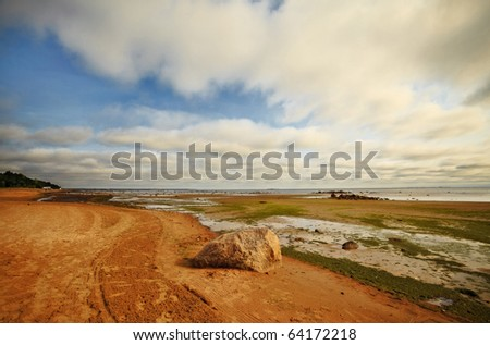 seashore with big stone under clouds